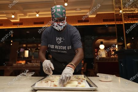 Sharon Holm, a volunteer from Food Rescue US, prepares cold cuts for sandwiches at Marcus Samuelsson's Red Rooster Restaurant during the new coronavirus pandemic, in the Overtown neighborhood of Miami. Samuelsson has partnered with chef Jose Andres' World Central Kitchen to distribute meals to those in need