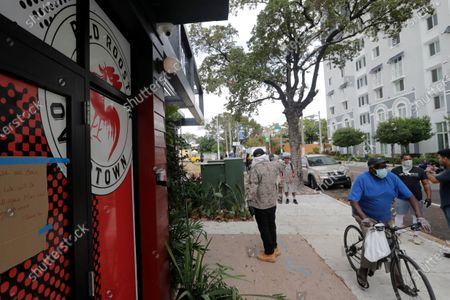 Man leaves Marcus Samuelsson's Red Rooster Restaurant after getting a free meal during the new coronavirus pandemic, in the Overtown neighborhood of Miami. Samuelsson has partnered with chef Jose Andres' World Central Kitchen to distribute meals to those in need