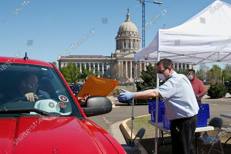 Paul Ziriax, right, Secretary of the Oklahoma State Election Board, wears a mask and gloves and practices social distancing due to COVID-19 concerns as he takes filing paperwork from state Sen. Paul Scott, left, R-Duncan, at a drive-thru registration area outside the state Capitol, in Oklahoma City. The new coronavirus causes mild or moderate symptoms for most people, but for some, especially older adults and people with existing health problems, it can cause more severe illness or death