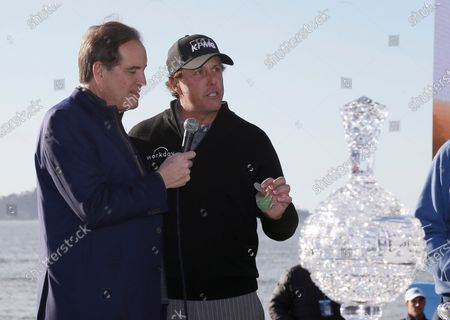 While being interviewed by broadcaster Jim Nantz, left, Phil Mickelson holds up a silver dollar that belonged to his grandfather during an awards ceremony on the 18th green of the Pebble Beach Golf Links after winning the AT&T Pebble Beach Pro-Am golf tournament, in Pebble Beach, Calif. Nantz has worked the Final Four and Masters for the last 34 years and is missing them in 2020 because of the new coronavirus pandemic