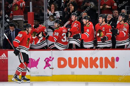 Chicago Blackhawks' Patrick Kane (88) celebrates with teammates on the bench after scoring a goal during the third period of an NHL hockey game against the San Jose Sharks in Chicago. While the coronavirus pandemic circles the world, sports business executives are having conversations about lucrative advertising and marketing contracts with no games on the horizon