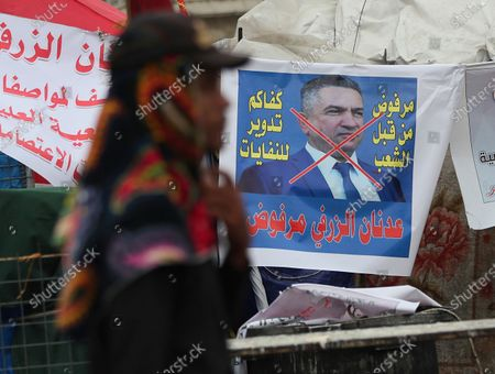 An anti-government protester passes a defaced picture of Iraq's then Prime Minister-designate Adnan Al-Zurfi, in Tahrir Square, Baghdad, Iraq. On Thursday, April 9, 2020, Mustafa al-Kadhimi, Iraq's intelligence chief, has been appointed the country's third prime minister-designate in just over a month. The appointment comes after the resignation of Al-Zurfi, Thursday amid political infighting. The upheaval threatened a leadership vacuum at the helm of the government amid a severe economic crisis and viral pandemic