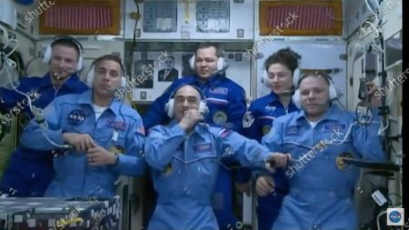 In this image from video made available by NASA, newly-arrived International Space Station crew members, foreground from left, Chris Cassidy, Anatoly Ivanishin and Ivan Vagner, stand with outgoing crew members, background from left, Andrew Morgan, Oleg Skripochka, and Jessica Meir during a news conference on