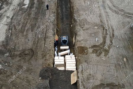 Workers wearing personal protective equipment bury bodies in a trench on Hart Island, in the Bronx borough of New York. On Thursday, New York City's medical examiner confirmed that the city has shortened the amount of time it will hold on to remains to 14 days from 30 days before they will be transferred for temporary internment at a City Cemetery. Earlier in the week, Mayor Bill DeBlasio said that officials have explored the possibility of temporary burials on Hart Island, a strip of land in Long Island Sound that has long served as the city's potter's field