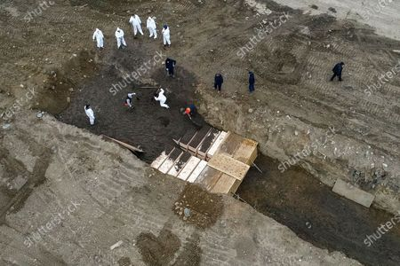 Workers wearing personal protective equipment bury bodies in a trench on Hart Island, in the Bronx borough of New York. New York City Mayor Bill DeBlasio said earlier in the week that officials have explored the possibility of temporary burials on Hart Island, a strip of land in Long Island Sound that has long served as the city's potter's field. The city's 2008 Pandemic Influenza Surge Plan states that Hart Island would be used as a temporary burial site in the event the death toll reaches the tens of thousands and if other storage, such as the refrigerator trucks parked outside hospitals, is full