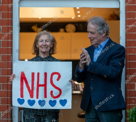 Recovering cancer patient Paul Morgan 76 and his wife Carolyn 84 from Wandsworth who have been self-isolating for 4 weeks clap for the NHS as millions of Brits around the country applaud the NHS and frontline workers this evening as Prime Minister Boris Johnson leaves ICU department at St Thomas's Hospital.