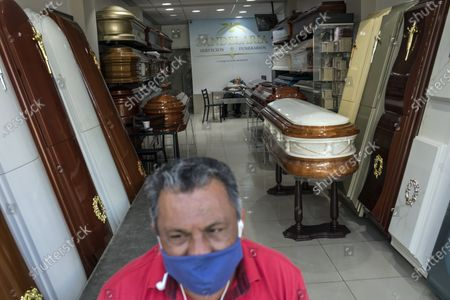 Employee Raul Gonzalez, 59, wearing a protective face mask, waits for clients at the entrance of the Candelabra funeral home as his boss Epifanio Gizaldo naps in the background, during the nationwide lockdown imposed by the government due to the COVID-19 pandemic in Lima, Peru. Business has fallen for funeral homes that specialize in selling coffins for victims of violent crime, road accidents or other types of street crimes since the nationwide quarantine to help curb the spread of the new coronavirus