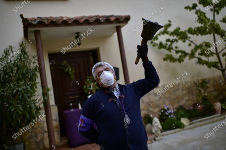 "Jose Mari Perez, 59, a member of ""Santa Vera Cruz'' brotherhood known as ''Los Picaos'' wears a face mask, as he rings a bell outside of his house on Maundy Thursday after celebrations were cancelled due to the outbreak of coronavirus, in San Vicente de La Sonsierra, northern Spain, . COVID-19 causes mild or moderate symptoms for most people, but for some, especially older adults and people with existing health problems, it can cause more severe illness or death"