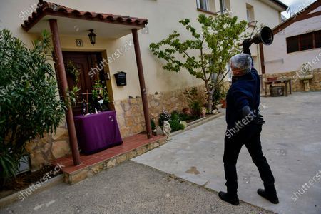 "Jose Mari Perez, 59, a member of ""Santa Vera Cruz'' brotherhood known as ''Los Picaos'' wears face protection, as he rings a bell outside of his house on Maundy Thursday after celebrations were cancelled due to the outbreak of coronavirus, in San Vicente de La Sonsierra, northern Spain, . COVID-19 causes mild or moderate symptoms for most people, but for some, especially older adults and people with existing health problems, it can cause more severe illness or death"