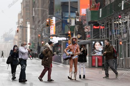 """Street performer Robert John Burck, known as The Naked Cowboy, draws a crowd of photographers in New York's Times Square, during the coronavirus epidemic. He is wearing a mask and his guitar is adorned with stickers that read, """"Trump Keep America Great"""
