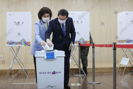 Seoul Mayor Park Won-soon (R) and his wife, Kang Nan-hee (L), cast a ballot while wearing plastic gloves to prevent virus infection at a polling station on the first day of the two-day early voting for the 15 April general elections, in Jongno, Seoul, South Korea, 10 April 2020.