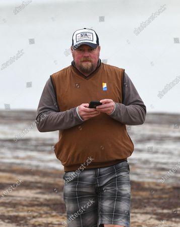 Trainer John McArdle looks on during a trackwork session at Balnarring Beach in Balnarring, Australia, 10 April 2020.