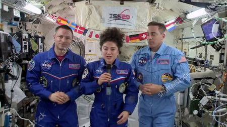 In this image from video made available by NASA, U.S. astronaut Jessica Meir speaks, accompanied by Andrew Morgan and Chris Cassidy, during a news conference held by the American members of the International Space Station on . Meir and Morgan said they expect it will be tough returning to such a drastically changed world next week, after a half-year or more in space