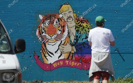 """Man looks at a mural depicting Joseph Maldonado-Passage, also known as """"Joe Exotic,"""" in Dallas, . The Netflix series """"Tiger King,"""" has become popular watching during the COVID-19 outbreak. Maldonado-Passage was convicted in an unsuccessful murder-for-hire plot"""