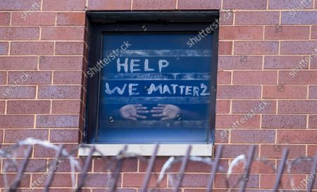 An inmate in the maximum security unit of the Cook County Jail presses his hands against the window below a plea for help in Chicago, Illinois, USA, 10 April 2020. The jail with nearly 4500 inmates has been hit hard by the coronavirus SARS-CoV-2 which causes the COVID-19 disease and is reportedly has the most infections of any single location in the US. Health officials have warned about overcrowding and unsanitary conditions at the nation's jails and prisons.