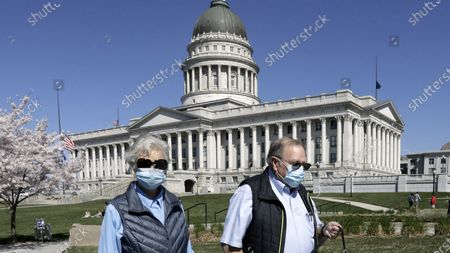 Alan and Vickie Eastman walk around the Utah State Capitol, in Salt Lake City. Utah Gov. Gary Herbert is extending his voluntary directive telling people to stay home except for essential errands through the end of April. He is also encouraging people to wear masks when at stores and other businesses to prevent the spread of the virus