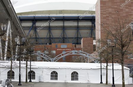 A tented walkway leading to a temporary hospital facility in one of the practice buildings at the USTA Billie Jean King National Tennis Center with Arthur Ashe Stadium in the background in Queens, New York, USA, 10 April 2020. The hospital, set up on the grounds where the US Open tennis tournament is held annually, has 475 beds, including 20 for ICU patients and will handle some COVID-19 patients starting today to help alleviate the stress on traditional area hospitals.