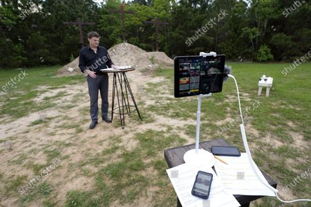 Senior Pastor Jason J. Nelson livestreams a Good Friday service outside Rose Hill United Methodist Church, in Tomball, Texas. The church has been broadcasting services during the COVID-19 outbreak