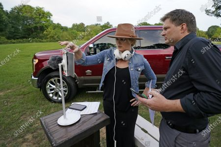 Senior Pastor Jason Nelson, right, and his wife, Tiffany, prepare to livestream a Good Friday service outside Rose Hill United Methodist Church, in Tomball, Texas. The church has been broadcasting services during the COVID-19 outbreak