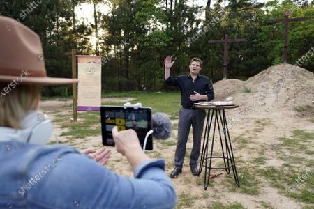 Senior Pastor Jason Nelson, right, conducts a Good Friday service as his wife, Tiffany, controls a livestream outside Rose Hill United Methodist Church, in Tomball, Texas. The church has been broadcasting services during the COVID-19 outbreak