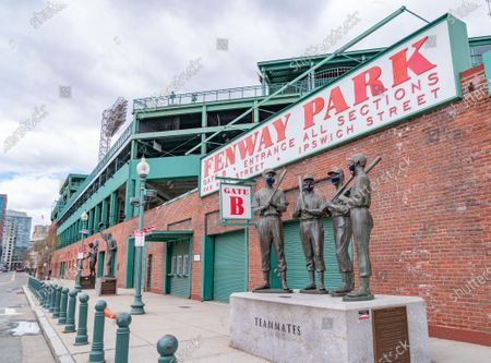 Ted Williams, Bobby Doerr, Johnny Pesky and Dom DiMaggio wearing face masks on the Teammates statue, created by sculptor Antonio Tobias Mendez, outside Fenway Park in Boston.