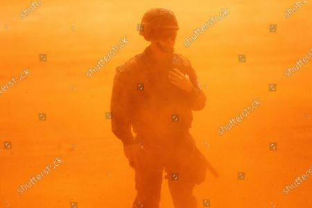 A Brazilian Air Force soldier is covered in dust during the landing of the Brazilian President Jair Bolsonaro's helicopter to the area where the construction of the first Union field hospital is being carried out, in Aguas Lindas de Goias, in the surroundings of Brasilia, Brazil, 11 April 2020. The location was chosen after a request for government support from the Goias state to the Union due to the need to pay special attention to COVID-19 in the region. The hospital begins to complement the health systems of Goias and the Federal District.