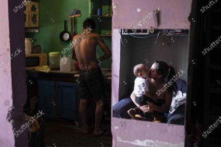 A man (L), unemployed due to the coronavirus crisis, does housework as a woman reflected in a mirror (R) kisses a child, in San Jose, Costa Rica, 10 April 2020 (Issued 11 April 2020). A desolate San Jose, in isolation due to sanitary measures to confront COVID-19, overexposes the most vulnerable: refugees, the indigent and the population in poverty.