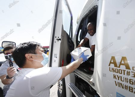 Stock Picture of Kavkaz Express employee Bakha Tokkozhin, left, hands a box of food to truck driver Jerry Hall of Dallas, who was headed to Las Vegas with his load, as a gesture of thanks and support for drivers' work during the outbreak of the new coronavirus at the Flying J Truck Stop, in Aurora, Colo. The new coronavirus causes mild or moderate symptoms for most people, but for some, especially older adults and people with existing health problems, it can cause more severe illness or death