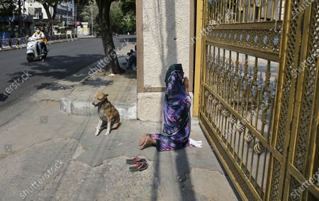 Stock Photo of An Indian woman offers Easter prayers from outside the closed gates of Saint Mary's Basilica in Hyderabad, India, . People around the world are celebrating Easter from the safety of their homes in an effort to help arrest the coronavirus outbreak