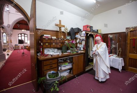Father Tom Devlin prepares to celebrate Easter Sunday mass at St Bridget's RC Church in the parish of St Ambrose in Baillieston, Glasgow, Scotland, 12 April 2020. Due to the Covid-19 pandemic he streamed the service live via Facebook to parishioners.
