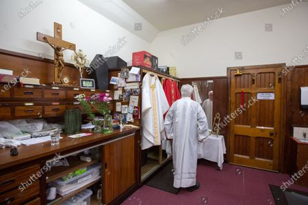 Father Tom Devlin puts on his vestments as he prepares to celebrate Easter Sunday mass at St Bridget's RC Church in the parish of St Ambrose in Baillieston, Glasgow, Scotland, 12 April 2020. Due to the Covid-19 pandemic he streamed the service live via Facebook to parishioners.