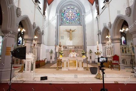 Father Tom Devlin celebrates Easter Sunday mass at St Bridget's RC Church in the parish of St Ambrose in Baillieston, Glasgow, Scotland, 12 April 2020.  Due to the Covid-19 pandemic he streamed the service live via Facebook to parishioners.