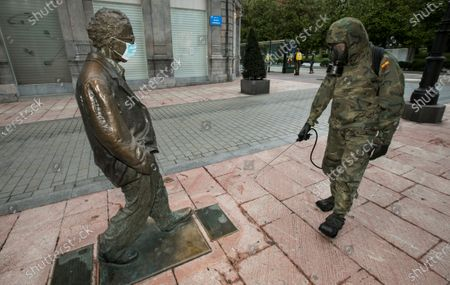 A Spanish soldier disinfects a statue of US director Woody Allen with a face mask in Oviedo, northern Spain, 12 April 2020. Spain is currently under lockdown due to the coronavirus pandemic.