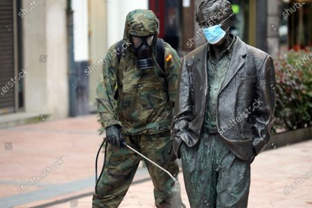 Oviedo, SPAIN: A Spanish Army soldier cleans the statue of Woody Allen during the 30th day of the State of Alarm in Spain, in Oviedo, Spain on April 12, 2020.