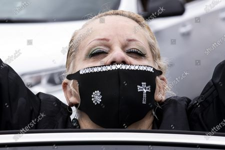 Stock Picture of Suzette Ramires reacts wearing a face mask with a cross sewed on during a drive-in Easter mass at the New Harvest Church amid the coronavirus pandemic in Norwalk, south of Los Angeles, California, USA, 12 April 2020.