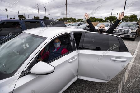 Stock Photo of Suzette Ramires (R) reacts wearing a face mask with a cross sewed on next to her husband Woody during a drive-in Easter mass at the New Harvest Church amid the coronavirus pandemic in Norwalk, south of Los Angeles, California, USA, 12 April 2020.