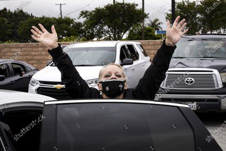 Suzette Ramires reacts wearing a face mask with a cross sewed on during a drive-in Easter mass at the New Harvest Church amid the coronavirus pandemic in Norwalk, south of Los Angeles, California, USA, 12 April 2020.