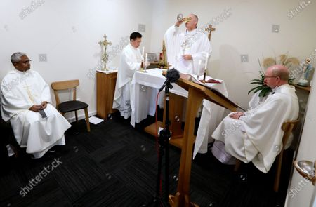 Bishop Paul Martin of the Catholic Diocese of Christchurch, center, takes communion during an online Easter Mass in a room at their diocese offices in Christchurch, New Zealand, . New Zealand is into week three of an unprecedented 28 day lockdown in a bid to stop the spread of the coronavirus