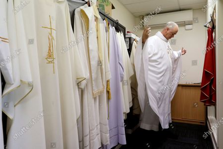 Bishop Paul Martin of the Catholic Diocese of Christchurch dresses ahead of an online Easter Mass at their diocese offices in Christchurch, New Zealand, .New Zealand is into week three of an unprecedented 28 day lockdown in a bid to stop the spread of the coronavirus