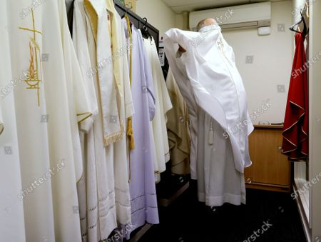 Bishop Paul Martin of the Catholic Diocese of Christchurch dresses ahead of an online Easter Mass at their diocese offices in Christchurch, New Zealand, . New Zealand is into week three of an unprecedented 28 day lockdown in a bid to stop the spread of the coronavirus