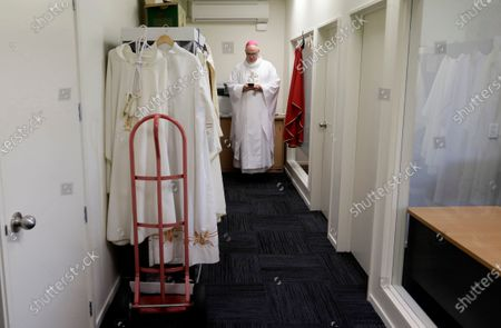 Bishop Paul Martin of the Catholic Diocese of Christchurch checks his mobile phone prior to an online Easter Mass in a room at their diocese offices in Christchurch, New Zealand, . New Zealand is into week three of an unprecedented 28 day lockdown in a bid to stop the spread of the coronavirus