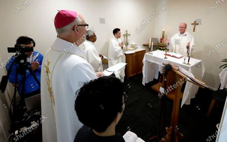 Stock Photo of Bishop Paul Martin of the Catholic Diocese of Christchurch, left, watches as father Simon Eccleston hosts an online Easter Mass in a room at their diocese offices in Christchurch, New Zealand, . New Zealand is into week three of an unprecedented 28 day lockdown in a bid to stop the spread of the coronavirus