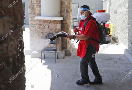 Stock Image of Amid concerns of the spread of COVID-19, Jose Antonio Sanchez sprays a disinfectant on a walkway area in front of El Rancho grocery store in Dallas