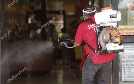 Amid concerns of the spread of COVID-19, Jose Antonio Sanchez sprays disinfectant on the entrance walkway in front of El Rancho grocery store in Dallas