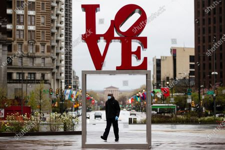 "Person wearing a protective face mask walks by the Robert Indiana sculpture ""LOVE"" at John F. Kennedy Plaza, commonly known as Love Park, in Philadelphia"