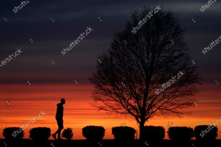 Man walks alone in a Kansas City, Mo., park at sunset, as stay-at-home orders continue in much of the country in an effort to stem the spread of the new coronavirus