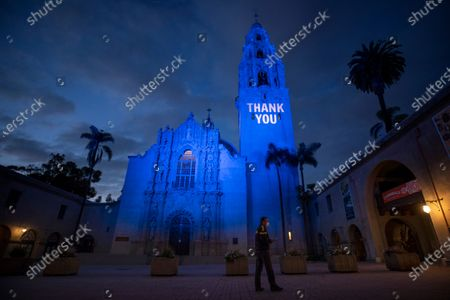 """John Bailey looks on after adjusting the blue light and """"Thank You"""" message on the California Tower and Museum of Man in honor of healthcare workers and first responders battling the new coronavirus in Balboa Park, in San Diego"""