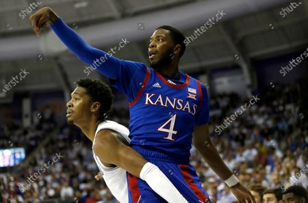 """Kansas guard Isaiah Moss (4) scores on a 3-point shot as TCU forward Diante Smith (10) looks on during the first half of an NCAA college basketball game in Fort Worth, Texas. In the eyes of many coaches, the NCAA transfer portal has made transferring too easy, giving players an easy out for any reason: amount of playing time, location, level of competition, even something as silly as school colors.""""There's a lot of juggling that has to take place because of the transfer portal,"""" said Kansas coach Bill Self, who lost elite guard Isaac McBride to Vanderbilt but enjoyed the benefit of getting sharp-shooter Isaiah Moss from Iowa this past season"""
