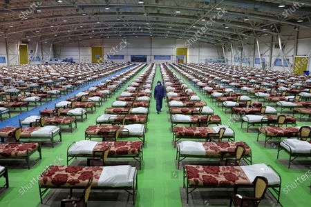 A member of the Iranian army walks past rows of beds at a temporary 2,000-bed hospital for coronavirus patients set up by the army at the international exhibition center in northern Tehran, Iran. Even as both face the same invisible enemy in the coronavirus pandemic, Iran and the U.S. remain locked in retaliatory pressure campaigns that now view the outbreak as just the latest battleground. Initially overwhelmed, Tehran now seeks to sway international opinion over U.S. sanctions by highlighting its struggles with COVID-19