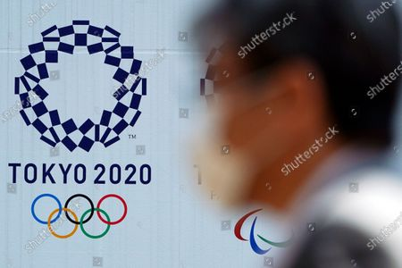 "A man wearing a face mask walks near the logo of the Tokyo 2020 Olympics, in Tokyo. Tokyo organizers said they have no ""B Plan"" for again rescheduling the Olympics, which were postponed until next year by the virus pandemic. They say they are going forward under the assumption the Olympics will open on July 23, 2021"